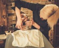 Cliente durante la rasatura della barba fotografia stock