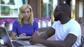 Cliente e empregado que discutem detalhes de projeto usando a tabuleta e o portátil filme