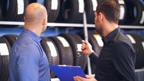 Cliente e vendedor no serviço do carro ou na auto loja vídeos de arquivo