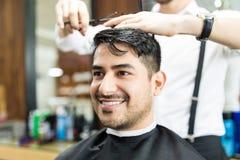 Cliente elegante que sonríe mientras que estilista que corta su pelo en salón foto de archivo