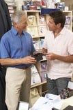 Cliente en almacén de ropa con las ventas auxiliares Imágenes de archivo libres de regalías