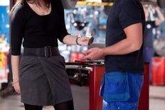Cliente en el departamento del mecánico que entrega clave Fotos de archivo libres de regalías