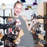 Cliente fêmea contente que guarda muitos pares de sapatas Foto de Stock Royalty Free