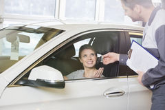 Cliente fêmea de sorriso que recebe a chave do carro do mecânico na oficina Fotografia de Stock Royalty Free