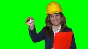 Cliente fêmea dos bens imobiliários que guarda a chave do apartamento novo no escritório do corretor de imóveis vídeos de arquivo