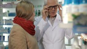 Cliente fêmea dos consultates masculinos do farmacêutico na drograria vídeos de arquivo