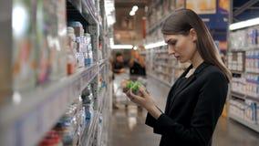 Cliente fêmea feliz que procura pelo comida para bebê no supermercado, mamã da mãe de Yong na loja Imagens de Stock