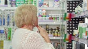 Cliente fêmea idoso que examina produtos médicos para a venda na drograria video estoque