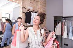 Cliente fêmea jovial que termina a compra na sala de exposições foto de stock