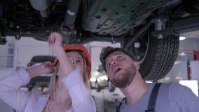 Cliente fêmea no capacete de segurança com o mecânico de carro que examina o automóvel levantado na estação do serviço de reparaç video estoque