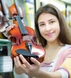 Cliente fêmea que compra violinos na loja Fotos de Stock