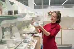 Cliente fêmea que escolhe pratos do utensílio na alameda do supermercado imagem de stock royalty free