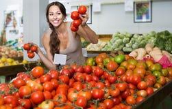 Cliente fêmea que guarda tomates maduros frescos no mercado Fotografia de Stock