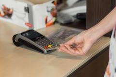 Cliente fêmea que paga pelo cartão de crédito no café Imagens de Stock