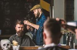 Cliente farpado do moderno que obt?m o penteado O barbeiro com hairdryer trabalha no penteado para o homem farpado, barbeiro foto de stock royalty free