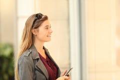 Cliente felice che guarda una stanza frontale di negozio tenere uno Smart Phone fotografia stock