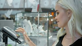 Cliente felice della donna in un terminale della carta di paga del negozio di gioielli senza contatto Immagine Stock