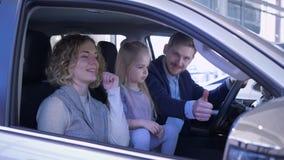 Cliente felice nel centro di vendite automatiche, famiglia sorridente con il bambino ispezionare nuova automobile e dare il polli