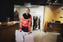 Cliente feliz con el panier en la sala de exposición de la moda Imagenes de archivo