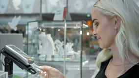 Cliente feliz da mulher em um terminal do cartão do pagamento da loja de joia sem contato Imagens de Stock Royalty Free