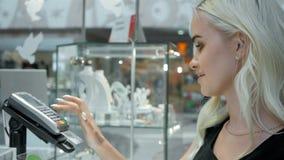 Cliente feliz da mulher em um terminal do cartão do pagamento da loja de joia sem contato Imagem de Stock
