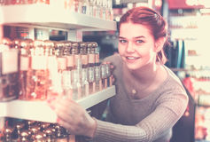 Cliente feliz da mulher que decide em variações do perfume nos cosméticos s Fotos de Stock Royalty Free