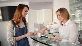 Cliente feliz da mulher que paga com o cartão de crédito na sala de exposições da forma A moça paga por seus artigos video estoque