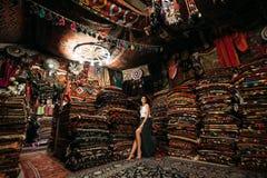 Cliente feliz de la mujer que elige la alfombra coloreada en tienda de la alfombra imagen de archivo