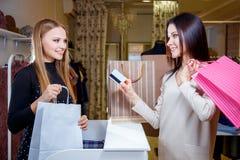 Cliente feliz de la mujer que paga con la tarjeta de crédito en tienda de la moda Fotografía de archivo libre de regalías