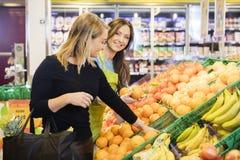 Cliente feliz de Standing By Female de la dependienta que elige naranjas imagen de archivo libre de regalías