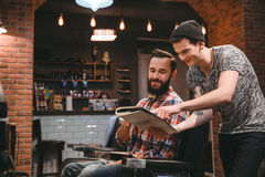 Cliente feliz do barbeiro e do índice que olha através do compartimento fotos de stock royalty free