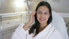 Cliente feliz en salón de belleza, muchacha hermosa del retrato en la albornoz que miente en el sofá después de procedimiento en  almacen de video