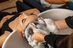 Cliente feliz en un salón de pelo que se lava el pelo con champú fotografía de archivo