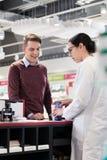 Cliente feliz que escucha las recomendaciones de un farmacéutico confiable imagen de archivo