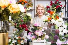 Cliente femenino alegre adulto que elige las flores Imágenes de archivo libres de regalías