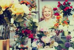 Cliente femenino alegre adulto que elige las flores Fotos de archivo