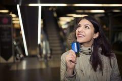 Cliente femenino con compras plásticas de la tarjeta en la alameda Mujer adolescente joven que usa la tarjeta de crédito de los p Foto de archivo libre de regalías