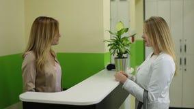 Cliente femenino de la reunión del recepcionista en salón de belleza metrajes