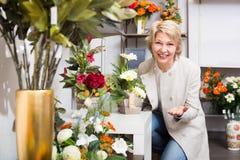 Cliente femenino de risa que elige las flores Imagenes de archivo
