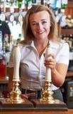 Cliente femenino de Serving Drink To del camarero Imagenes de archivo