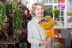 Cliente femenino del jubilado adulto que elige las flores Fotografía de archivo libre de regalías