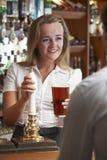 Cliente femenino del varón de Serving Drink To del camarero Imagen de archivo libre de regalías