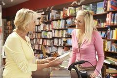 Cliente femenino en librería Fotos de archivo libres de regalías
