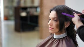 Cliente femenino encantador del primer medio en la barbería durante el pelo que diseña por el peluquero profesional almacen de video