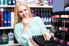 Cliente femenino feliz que compra lápiz labial rojo Imagenes de archivo