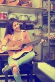 Cliente femenino joven que intenta tocar la guitarra Fotos de archivo libres de regalías