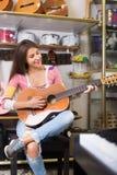 Cliente femenino joven que intenta tocar la guitarra Foto de archivo