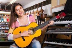 Cliente femenino joven que intenta tocar la nueva guitarra Imagen de archivo libre de regalías