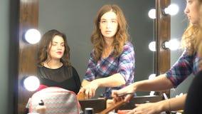 Cliente femenino joven que mira en el espejo mientras que artista de maquillaje que trabaja en sus ojos en salón de belleza almacen de video