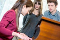 Cliente femenino joven sonriente que elige el sintetizador en tienda Imagenes de archivo